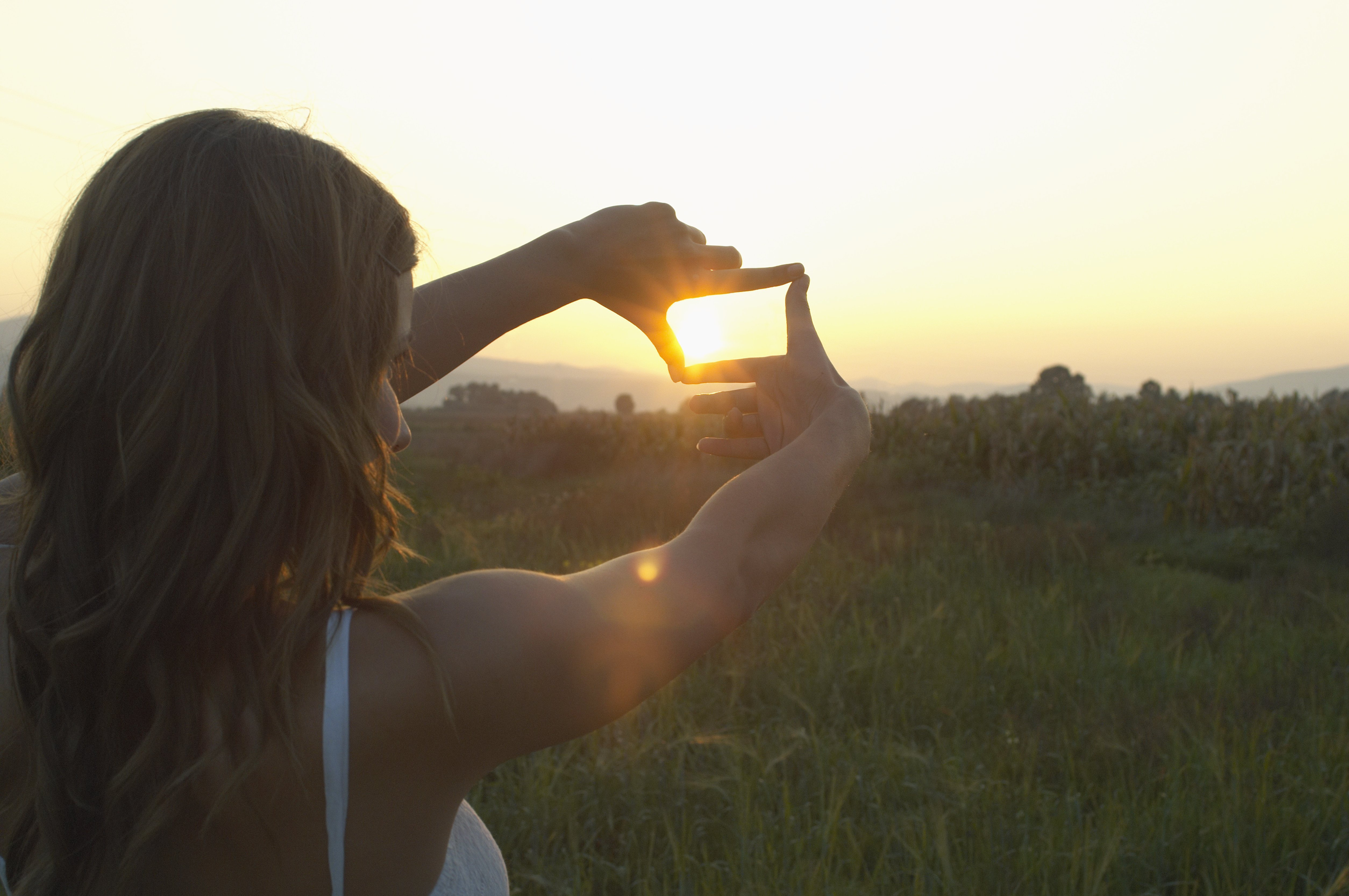 Teenage girl (16-18) outdoors, framing sun with fingers